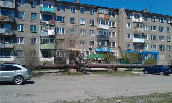 カザフスタンの水道管の上を渡る人