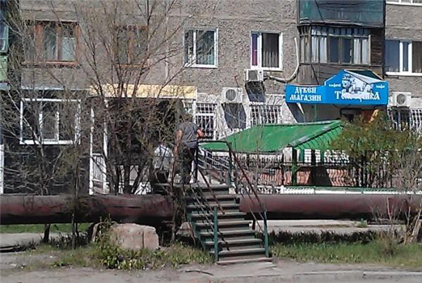 カザフスタンの水道管の上を渡る人(拡大)